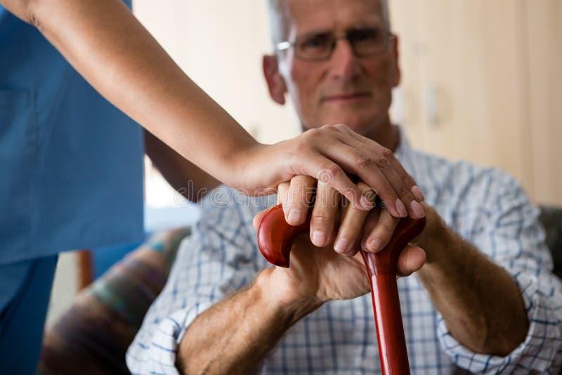 Chiuda su delle mani dell'uomo senior e di medico femminile che tengono la canna di camminata fotografie stock