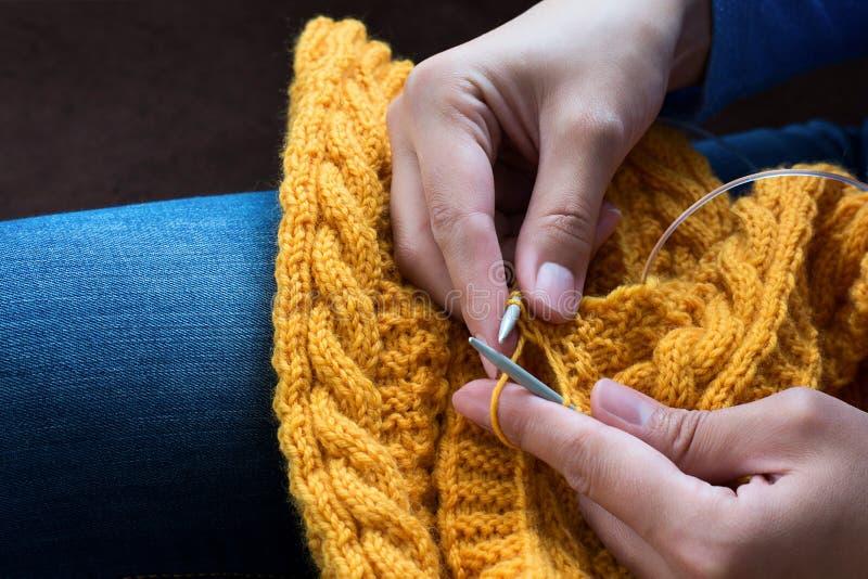 Chiuda su delle mani della donna che tricottano il filato di lana variopinto fotografia stock libera da diritti