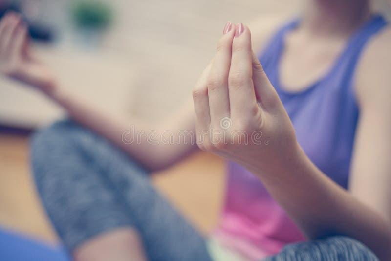 Chiuda su delle mani della donna, facendo l'yoga fotografia stock libera da diritti