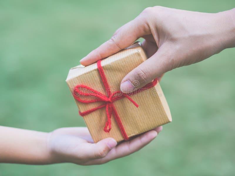 Chiuda su delle mani della madre e del bambino con il contenitore di regalo fotografia stock libera da diritti