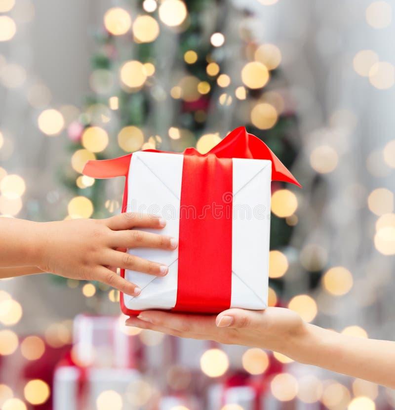 Chiuda su delle mani della madre e del bambino con il contenitore di regalo fotografia stock