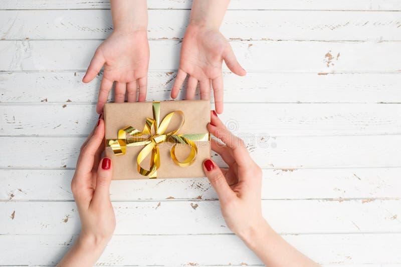 Chiuda su delle mani della madre e del bambino con il contenitore di regalo sopra fondo di legno immagine stock libera da diritti