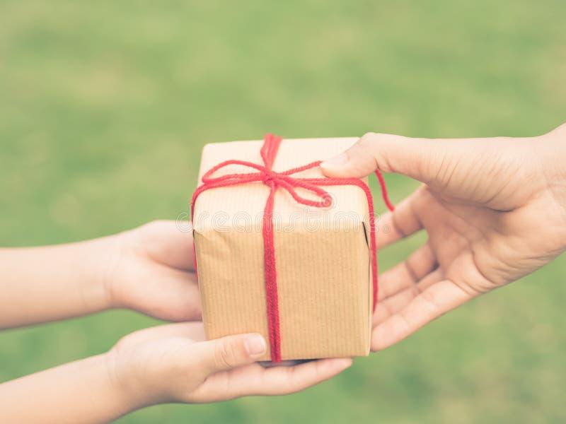 Chiuda su delle mani della madre e del bambino con il contenitore di regalo sopra fondo verde Stile dell'annata immagini stock libere da diritti