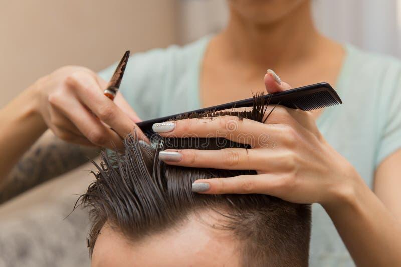 Chiuda su delle mani di giovane barbiere che fanno il taglio di capelli all'uomo attraente in parrucchiere fotografia stock