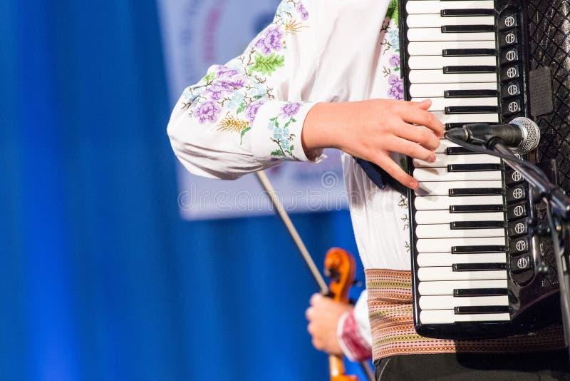 Chiuda su delle mani di giovane uomo rumeno eseguono una musica folk sulla fisarmonica in costume folclorico tradizionale Folclor immagini stock