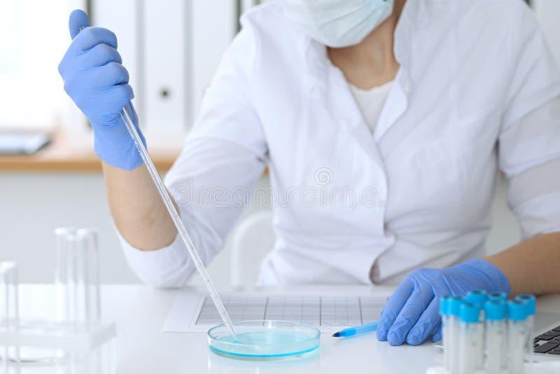 Chiuda su delle mani di ricerca scientifica con la chiara soluzione in laboratorio fotografia stock