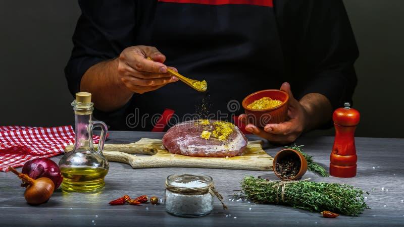 Chiuda su delle mani di un cuoco unico che preparano una bistecca con le spezie e le verdure Il concetto della ricetta di cottura fotografia stock libera da diritti