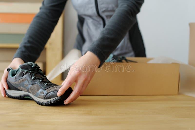 Chiuda su delle mani femminili che imballano le merci di sport Scarpe di sport fotografie stock