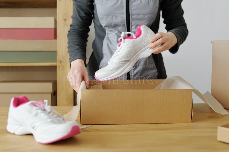 Chiuda su delle mani femminili che imballano le merci di sport Scarpe di sport immagini stock