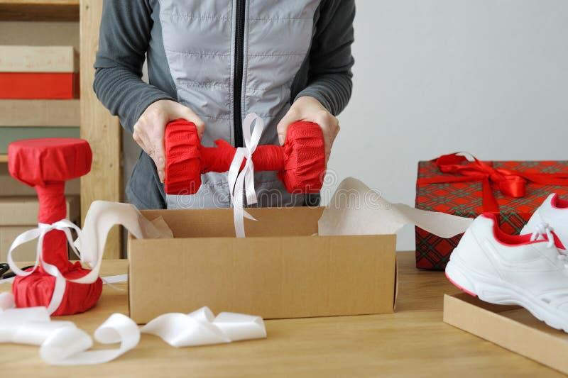 Chiuda su delle mani femminili che imballano le merci di sport Teste di legno per immagini stock