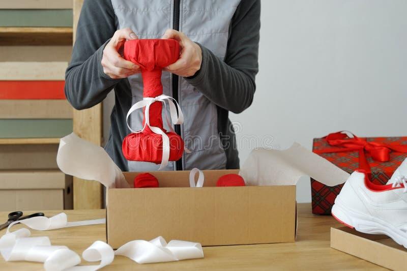Chiuda su delle mani femminili che imballano le merci di sport Teste di legno per fotografia stock libera da diritti