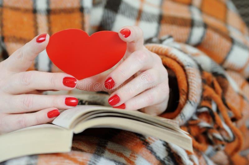 Chiuda su delle mani femminili che tengono il cuore rosso fotografia stock