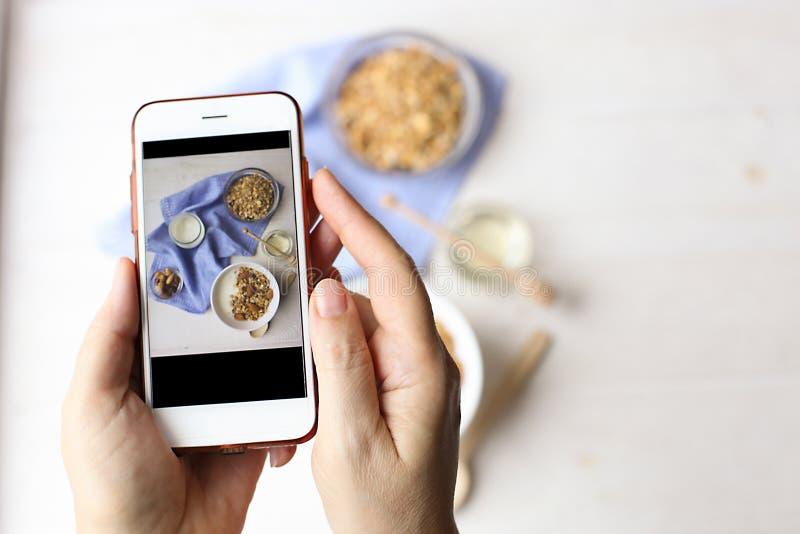 Chiuda su delle mani femminili che tengono il telefono cellulare che prende un'immagine dei cereali del granola, del yogurt del l immagini stock