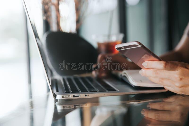 Chiuda su delle mani femminili facendo uso dello Smart Phone mentre lavorano al computer immagini stock libere da diritti