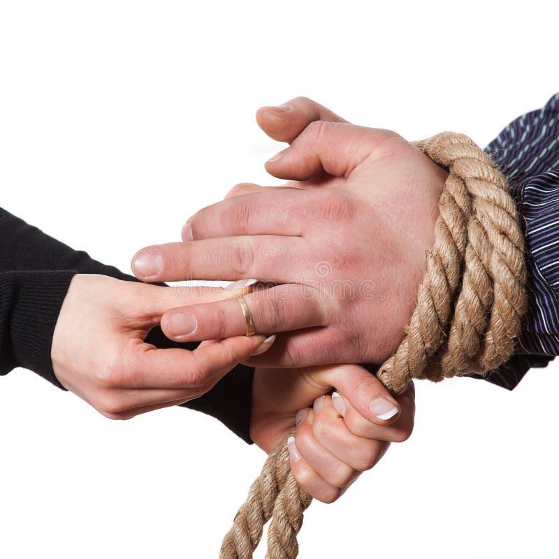 Chiuda su delle mani legate con la corda immagine stock libera da diritti