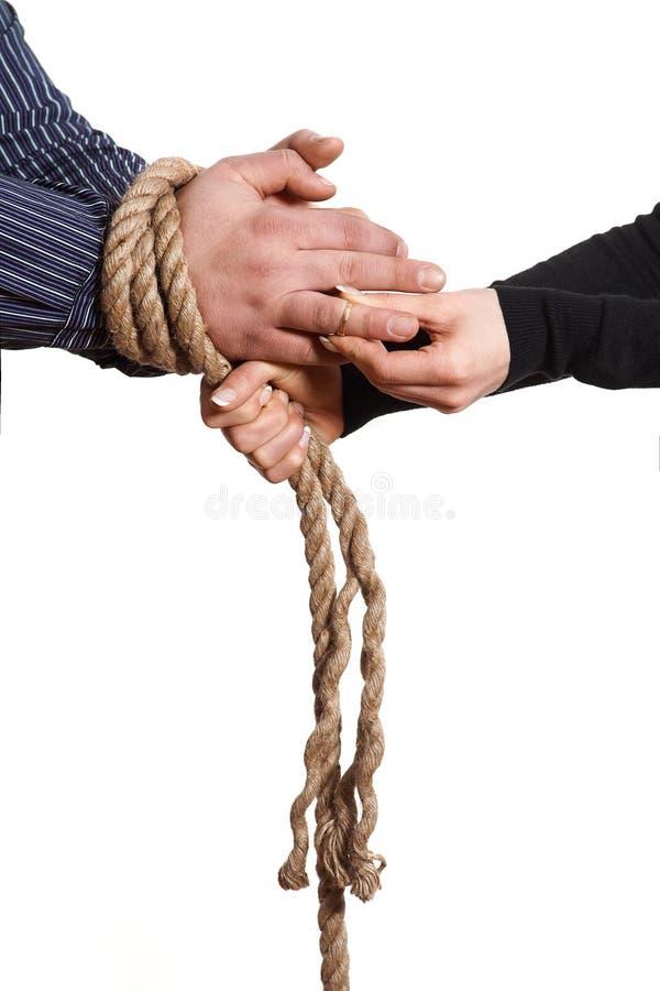 Chiuda su delle mani legate con la corda immagini stock libere da diritti