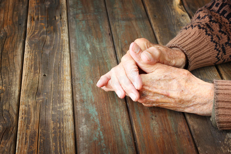 Chiuda su delle mani maschii anziane sulla tavola di legno immagine stock libera da diritti