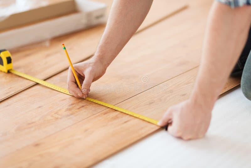 Chiuda su delle mani maschii che misurano la pavimentazione di legno fotografia stock libera da diritti