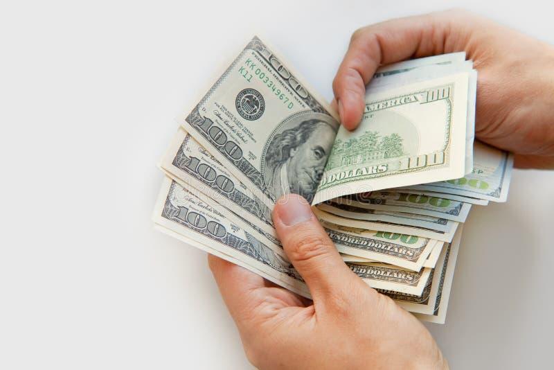 Chiuda su delle mani maschii con soldi immagine stock