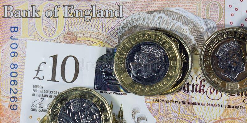 Chiuda su delle monete da una libbra su una nota da dieci libbre - valuta britannica immagine stock libera da diritti
