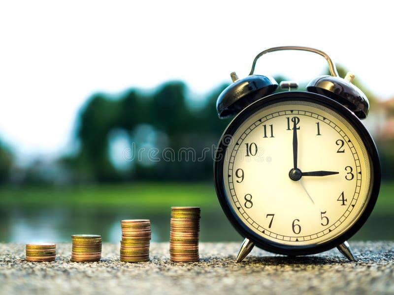 Chiuda su delle monete dei soldi della pila e di tempo, il valore di periodo del concetto dei soldi nel tema di finanza di affari fotografie stock