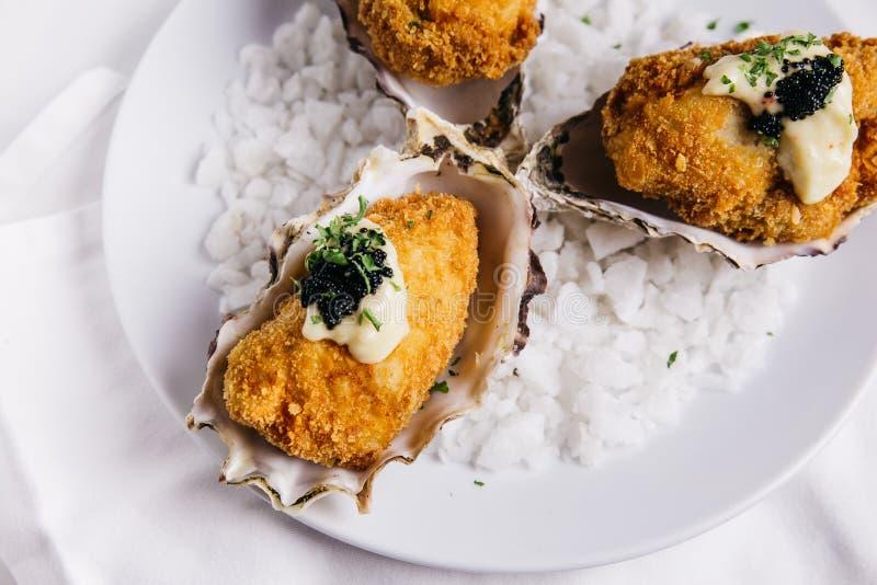 Chiuda su delle ostriche Deep fried che completano con la maionese ed il caviale serviti in piatto bianco con sale marino decorat fotografia stock