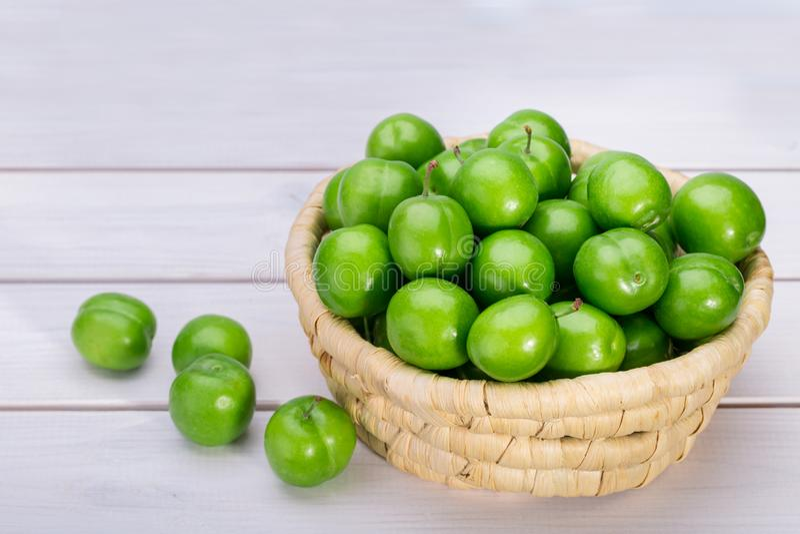 Chiuda su delle prugne o della susina Reine Claude verdi in un canestro isolato su Whi fotografia stock