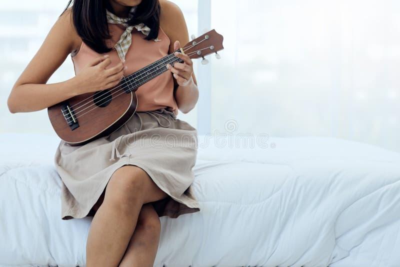 Chiuda su delle ukulele adolescenti sveglie asiatiche del gioco fotografia stock libera da diritti