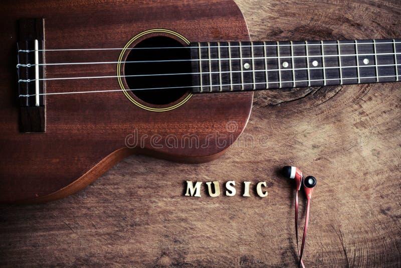Chiuda su delle ukulele e del trasduttore auricolare su vecchio fondo di legno fotografie stock