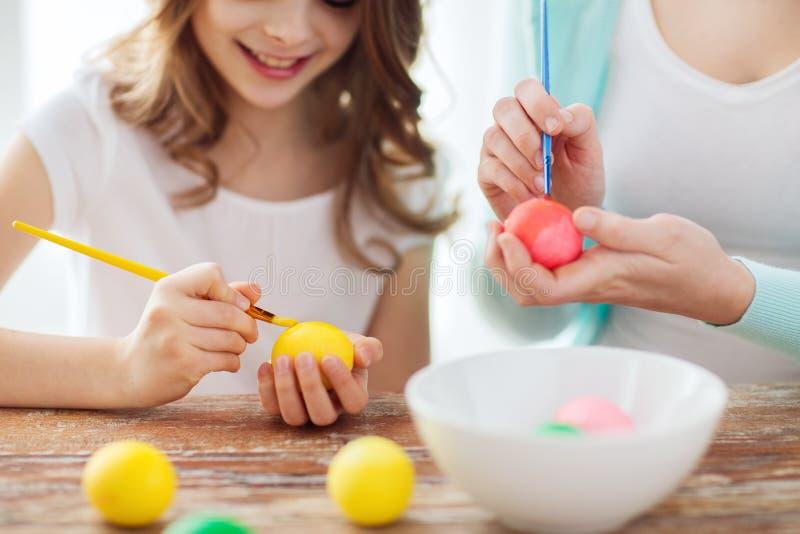 Chiuda su delle uova di coloritura della madre e della bambina immagine stock libera da diritti