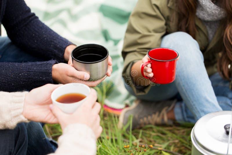 Chiuda su delle viandanti che bevono il tè dalle tazze al campo fotografia stock libera da diritti
