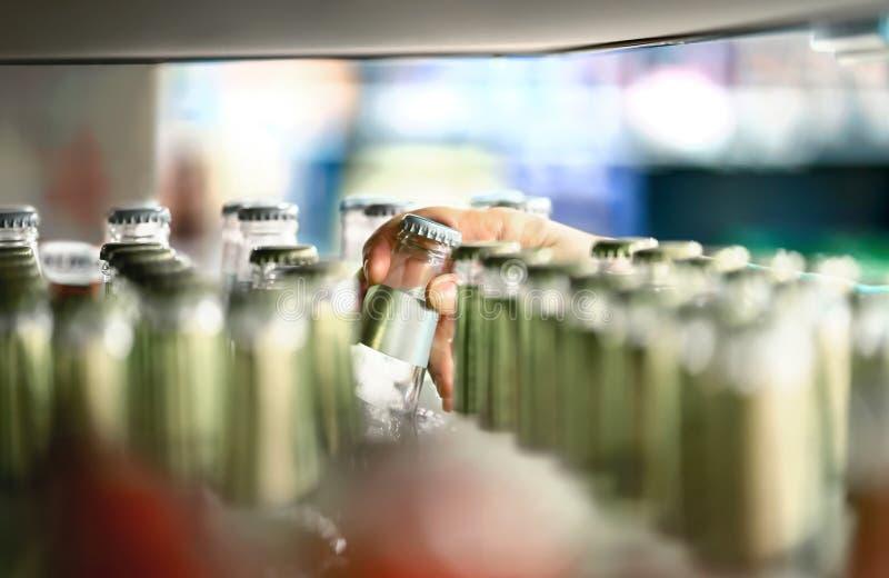 Chiuda su dello scaffale della bevanda in supermercato Bottiglia dell'alcool, della soda, del sodapop, dell'acqua minerale o del  fotografia stock libera da diritti
