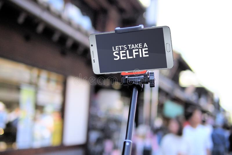 Chiuda su dello schermo vuoto dello smartphone con il bastone del selfie con il fondo della sfuocatura immagini stock libere da diritti