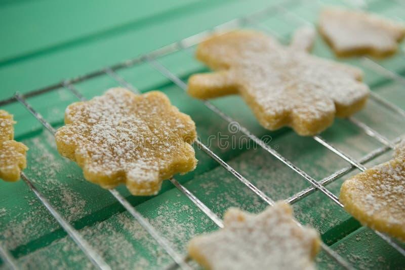 Chiuda su dello zucchero in polvere sui biscotti sopra lo scaffale di raffreddamento immagini stock