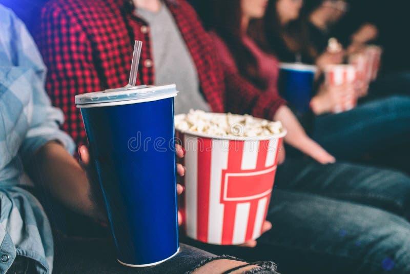 Chiuda su di alimento saporito ma non sano C'è canestro di popcorn e una tazza blu di coke sull'immagine L'uomo e la donna sono fotografie stock