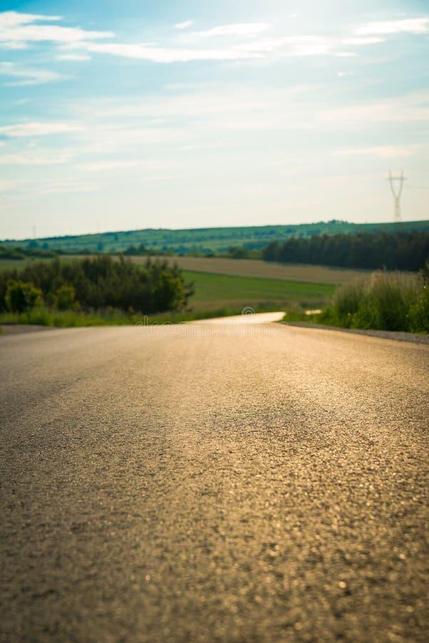 Chiuda su di asfalto sulla strada campestre Asfalti la struttura sulla strada rurale vuota gi? la collina immagine stock