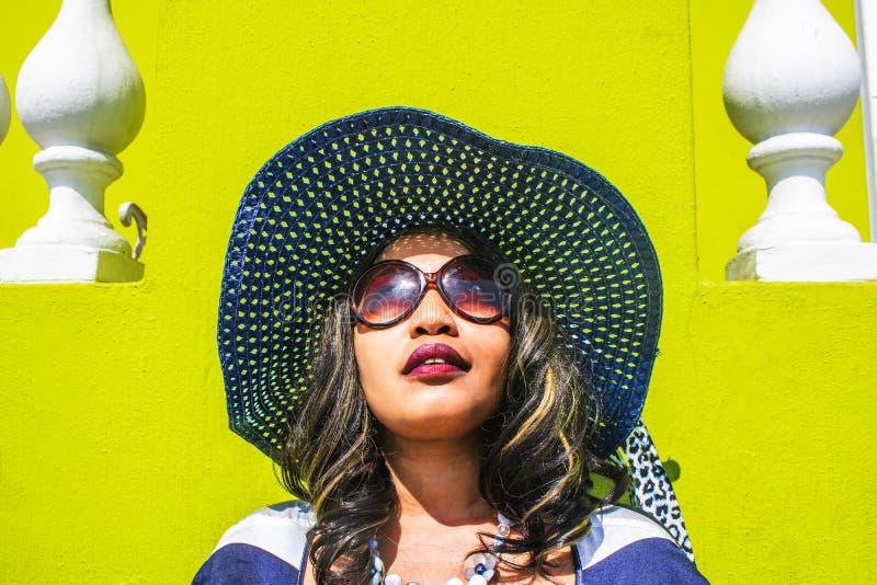 Chiuda su di bella donna africana in un vestito a strisce blu e bianco che modella davanti ad una casa tradizionale BO-Kaap con l fotografie stock libere da diritti