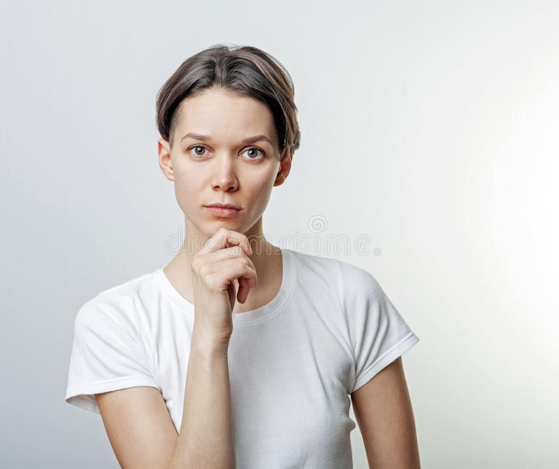 Chiuda su di bella, ragazza calma e attraente, un braccio sotto il mento, sembrare sicuro, flirtante, seducente, ha vestito casua fotografia stock