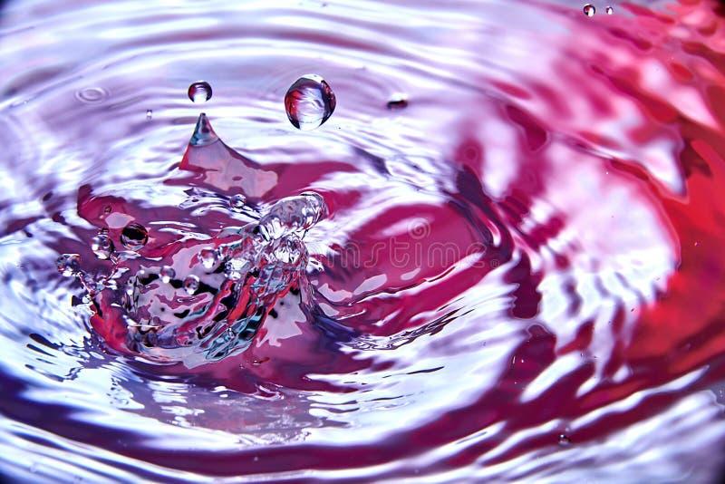 chiuda su di calo nell'acqua che rende differente spruzza fotografia stock