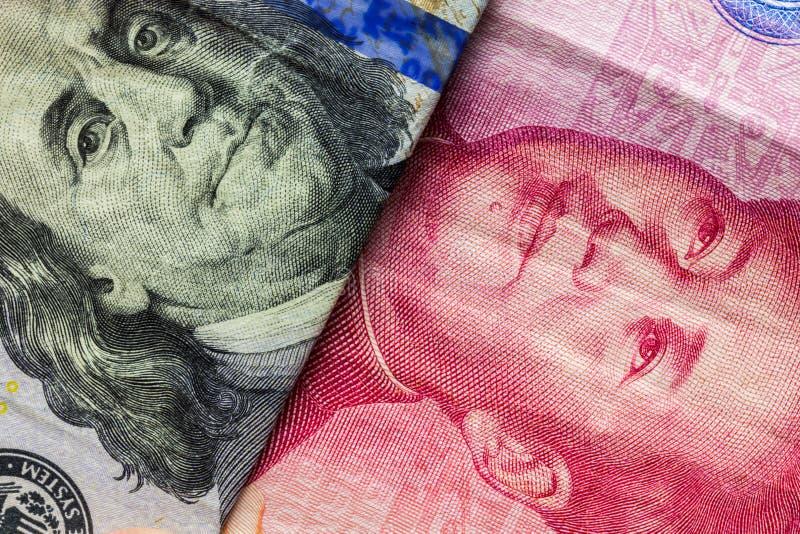Chiuda su di cento dollari e di 100 banconote di Yaun con il fuoco sui ritratti di Benjamin Franklin e di Mao Zedong /USA contro  immagine stock
