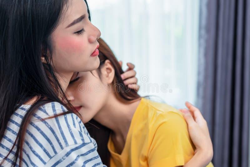 Chiuda su di due donne lesbiche asiatiche che abbracciano insieme nella camera da letto La gente delle coppie e concetto di belle fotografia stock