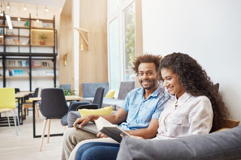 Chiuda su di due giovani in abbigliamento casual che si siede sul sofà in biblioteca moderna Ragazza che legge al libro, preparan immagini stock