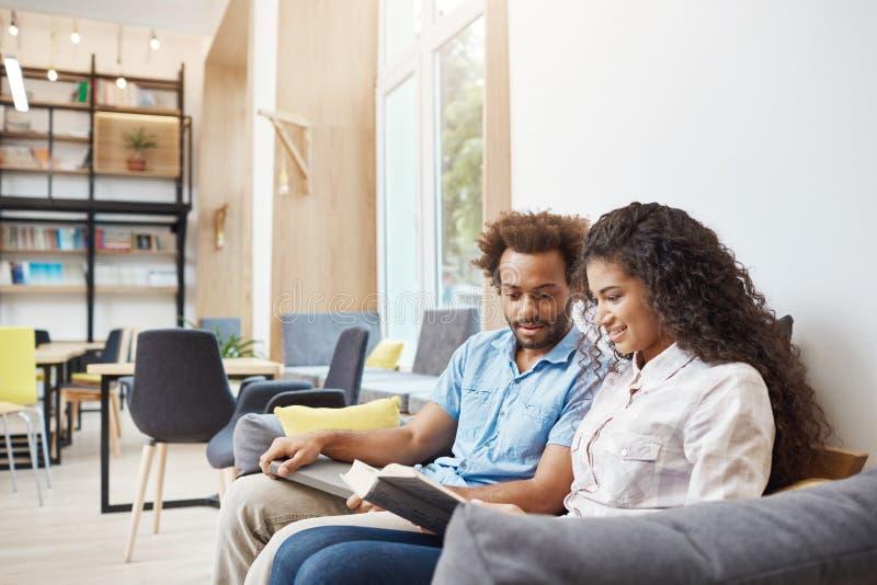 Chiuda su di due giovani studenti multi-etnici seri che si siedono sul sofà in biblioteca universitaria che guarda con le informa immagini stock