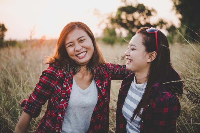Chiuda su di due ragazze Amici intimi nel campo con il backgr di tramonto immagini stock libere da diritti