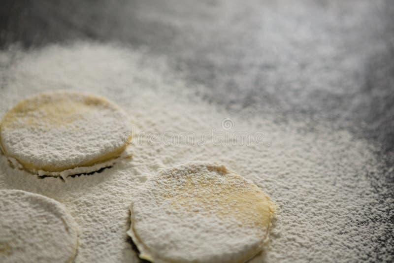Chiuda su di farina sui biscotti non cotti fotografie stock