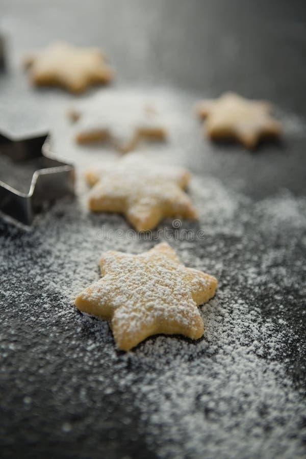 Chiuda su di farina sui biscotti non cotti di forma della stella immagine stock