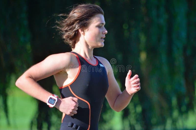 Chiuda su di funzionamento femminile di Triathlete in Skinsuit nero fotografia stock libera da diritti