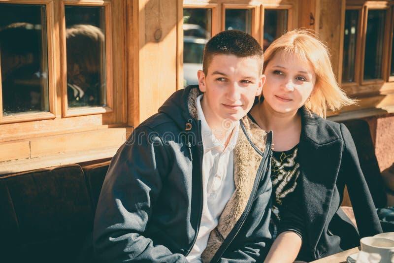 Chiuda su di giovane bella coppia sveglia che si siede insieme al caffè al giorno soleggiato, ritratto all'aperto sorridente feli fotografie stock