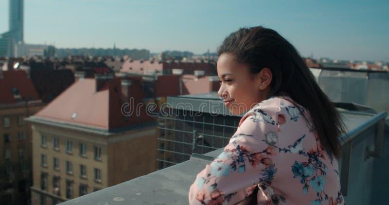 Chiuda su di giovane bella donna che gode del tempo su un tetto immagini stock