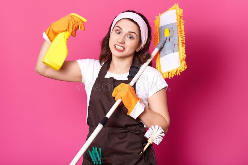 Chiuda su di giovane casalinga in guanti arancio, il grembiule marrone, la maglietta bianca, banda di divertimento dei capelli La immagini stock